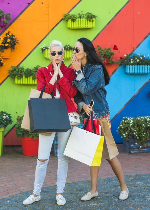 women in sunglasses with shopping bags