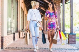women walking with sunglasses with shopping bags