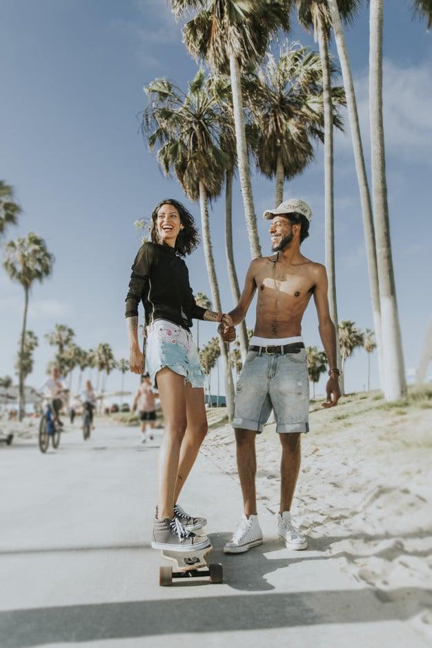 couple longboarding near beach